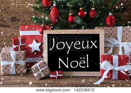 Colorful Christmas Card For Seasons Greetings. Christmas Tree With Balls And Snowflakes. Gifts In Front Of Wooden Background. Chalkboard With French Text Joyeux Noel Means Merry Christmas