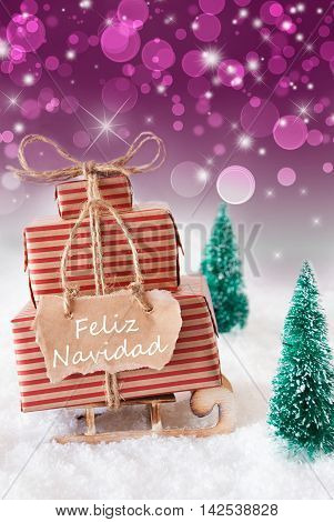 Vertical Image Of Sleigh Or Sled With Christmas Gifts Or Presents. Snowy Scenery With Snow And Trees. Purple Sparkling Background With Bokeh. Label With SpanishText Feliz Navidad Means Merry Christmas