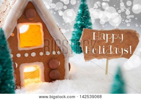Gingerbread House In Snowy Scenery As Christmas Decoration. Christmas Trees And Candlelight For Romantic Atmosphere. Silver Background With Bokeh Effect. English Text Happy Holidays