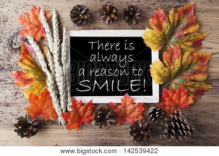 Blackboard With Autumn Or Fall Decoration. Greeting Card For Seasons Greetings. Colorful Leaves, Fir Cone And Barley On Aged Wooden Background. English Quote There Is Always A Reason To Smile