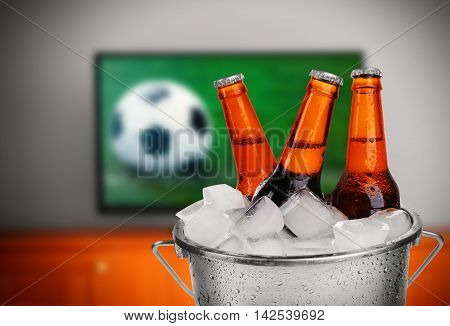 Bucket with ice and bottles of beer on wooden table in front of television show of football. Watching football match at home.Si