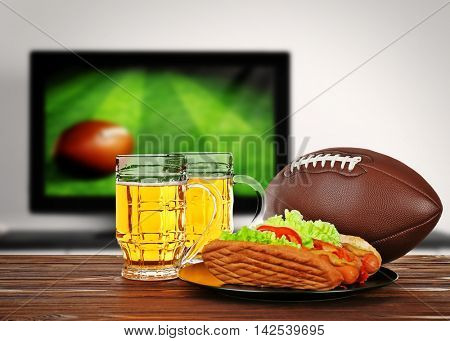 Two glasses of beer, ball and snack on wooden table in front of television show of football. Watching football match at home.