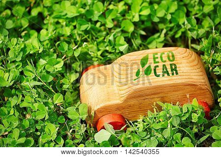 Wooden toy car with text eco car on grass. Transport and ecology concept.