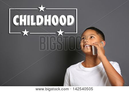 Cute afro american teenager with phone and text childhood on gray background. Childhood concept.