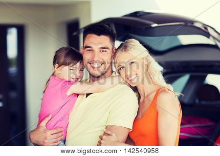 transport, leisure, road trip and people concept - happy family and little girl with hatchback car at home parking space