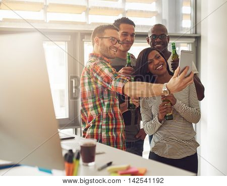 Diverse group of four happy young workers celebrating with beer and taking pictures with camera phone near desk with computer