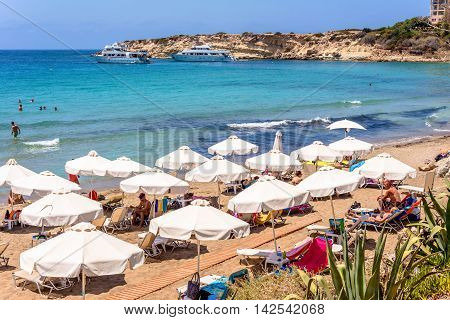 PAPHOS CYPRUS - JULY 24 2016: Tourists sunbeds and umbrellas on hot summer day at Coral Bay Beach.