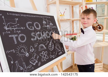 Boy during a lesson is at the blackboard and shows her pointer . concept of the lesson in school