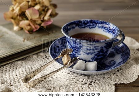 Close up of antique blue and white china cup and saucer with tea on lace cloth on wooden table with out of focus faded flower and old photograph album in background