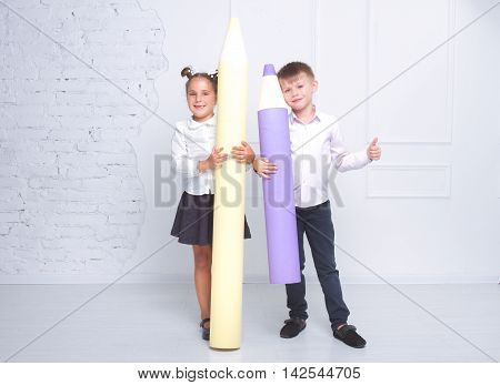 A boy and a girl dressed in a school uniform holding large pencils on white background. Large pencils - large knowledge. concept of education and children's knowledge