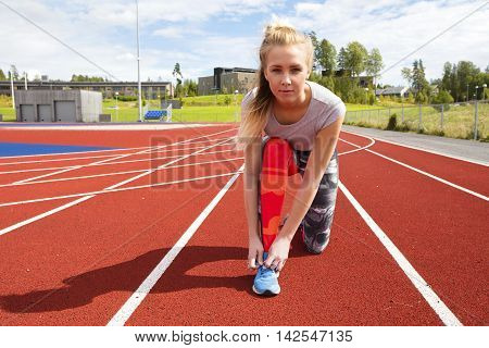 Fit athlete woman tying shoelaces on running track. Female sprinter prepares before running.