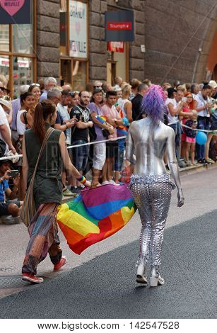STOCKHOLM SWEDEN - JUL 30 2016: Two woman carrying the rainbow pride flag one woman half naked covered with silver color in the Pride parade July 30 2016 in Stockholm Sweden