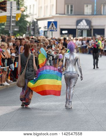 STOCKHOLM SWEDEN - JUL 30 2016: Two woman carrying the rainbow pride flag one woman half naked covered with silver body paint in the Pride parade July 30 2016 in Stockholm Sweden