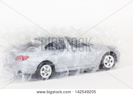 horizontal photo of a gray car toy with air bubble wrap on white background.