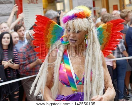 STOCKHOLM SWEDEN - JUL 30 2016: Old woman wearing a rainbow colored feathers in the Pride parade July 30 2016 in Stockholm Sweden