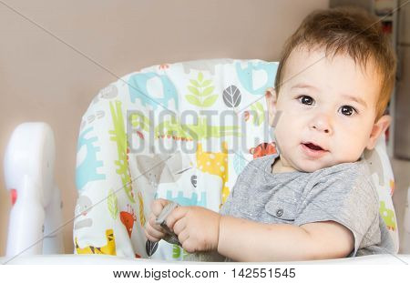 small happy child sitting in chair the concept of family child health feed the baby eat at home