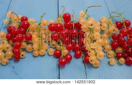 Red And White Currants On A Blue Board