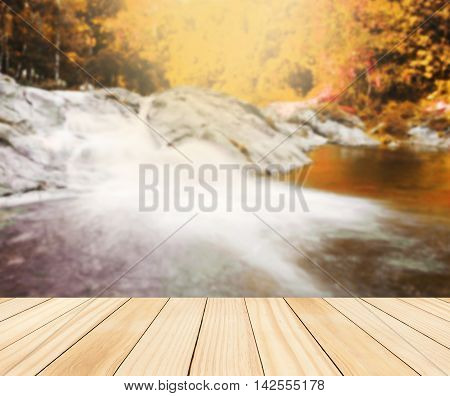 Wood table top on blurred colorful water fall Can be used for display or montage you product