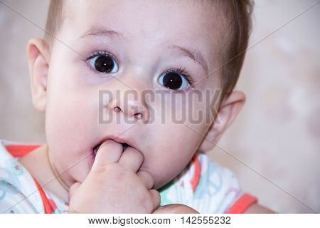 Baby boy plays with fingers in mouth and happy facial expression. Portrait a crawling smiling. Teething infant playing. Newborn child at home. The scratching his teeth.