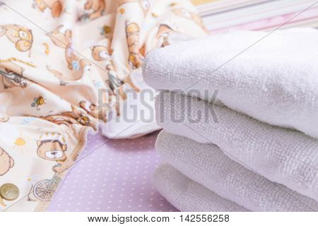 Modern eco stacks of cloth diapers and replacement bushings selective focus close-up bright background