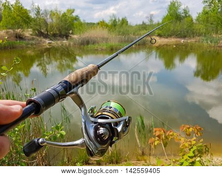 Fishing on the lake. Spinning reel and on a background of lake