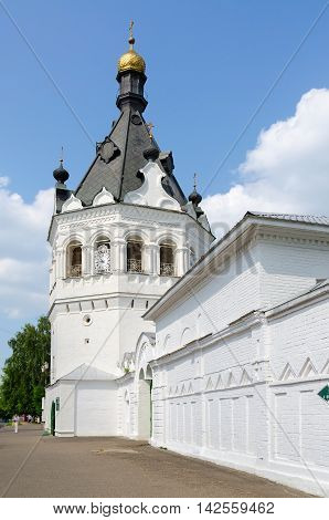 KOSTROMA RUSSIA - JULY 20 2016: Unidentified people walk down street along wall of Theophany Convent (tower of XVII century transformed in XIX century to monastery bell tower) Kostroma Russia