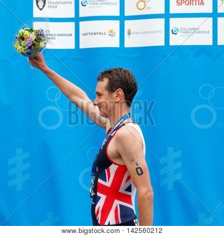 STOCKHOLM - JUL 02 2016: The gold medalist triathletes Alistair Brownlee holding flowers on the podium in the Men's ITU World Triathlon series event July 02 2016 in Stockholm Sweden