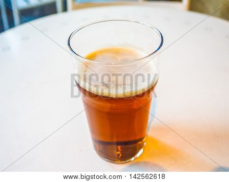 High dynamic range (HDR) Pint of British ale on a pub table - selective focus on beer over blurred background