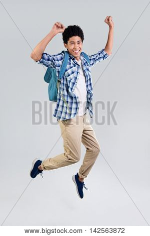 mixed race young man with backpack celebrating in mid air, movement jumping isolated in studio
