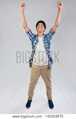 smiling mixed race young man overjoyed with arms raised isolated on grey background