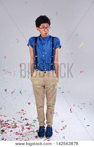 Nerd geek studious young man partying with confetti suspenders and glasses spectacles