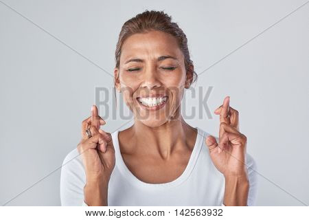 Headshot of mixed race woman wishing hoping with fingers crossed, expressions