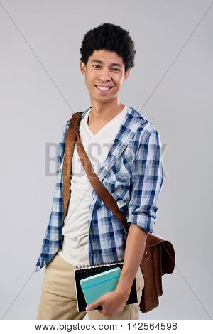 smiling mixed race student holding folders and books isolated on grey background