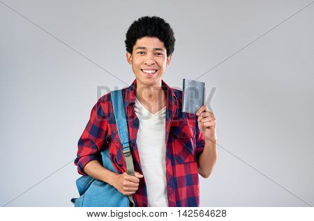 Young mixed race tourist man with afro holding passport visa on his way to travel adventure