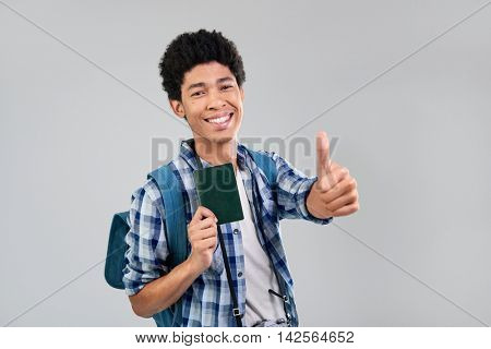 Happy tourist man with afro holding passport visa with thumbs up on his way to travel adventure