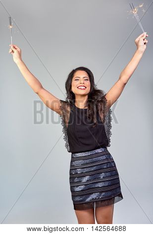 carefree happy woman having fun dancing at new years eve party while holding sparklers