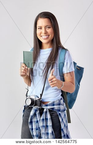 Happy tourist woman with camera holding passport in studio going on vacation, isolated on grey