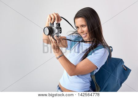 Mixed race woman taking a photo with vintage retro camera in studio, isolated on grey