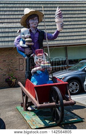 Ronks PA - July 23 2016: Katies is an Amish-owned and operated restaurant that includes a statue of an Amish boy holding an ice cream cone and two pigs.