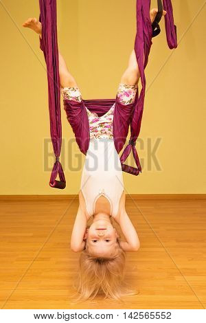 Little girl making aerial yoga exercises indoor fly yoga