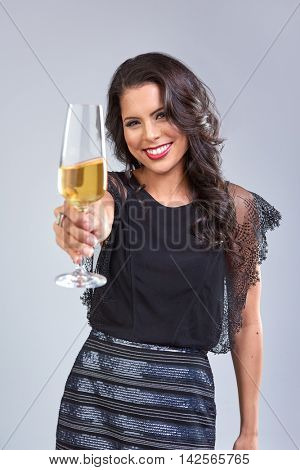 Young celebrating woman with red lips, cheers to camera holding champagne glass
