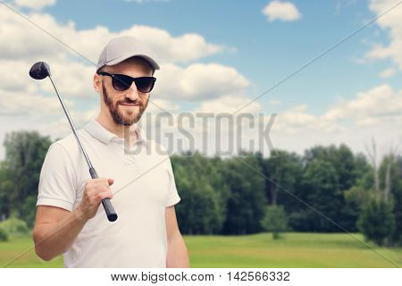Golfer man posing with golf club at golf course
