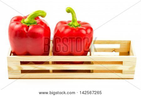Group of sweet red peppers in the wooden box isolated on white background