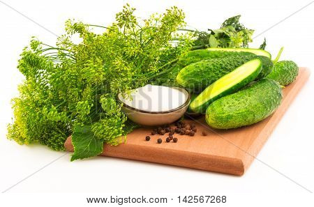 Cucumbers bloom dill with black pepper on the cutting board isolated on white background