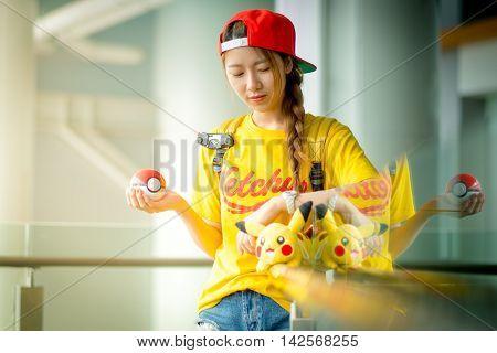 BANGKOK THAILAND – August 142016: Trainer girl playing pokemon pokemon ball and mobile pokemon go game app on smart phone gadget Lighting with sun flare