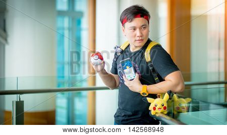 BANGKOK THAILAND – August 142016: Trainer boy playing pokemon pokemon ball and Pokemon Go gameplay screenshot on the phone Lighting with sun flare