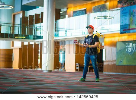 BANGKOK THAILAND – August 142016: Trainer boy playing pokemon pokemon ball playing at Gym Pokemon location Lighting with sun flare