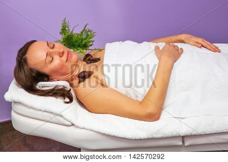 Adult woman laying on a massage table spa procedure with snails