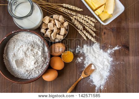 Selection of all necessary products for the preparation of dough - milk, butter, eggs, sugar, flour. On wooden table, top view, copy space