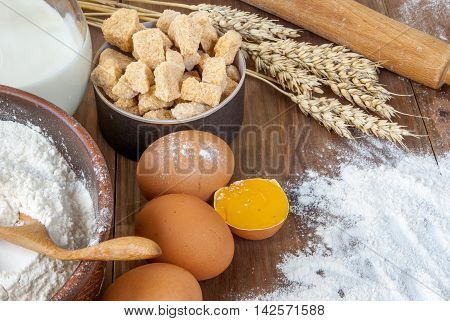 Selection of all necessary products for the preparation of dough - milk, butter, eggs, sugar, flour. On wooden table